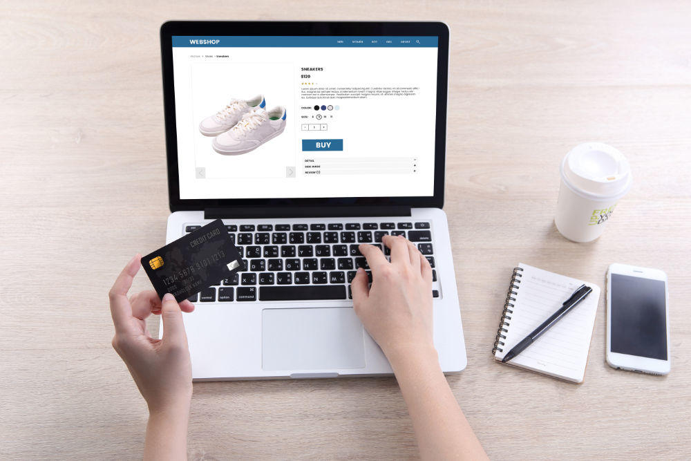 Woman use ecommerce webshop for buy shoes with holding credit card